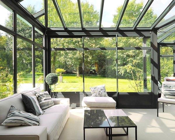 Veranda vetro con profili in alluminio scuro adibita a soggiorno